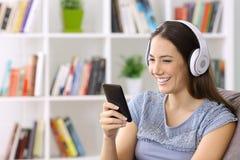 Muchacha que escucha la música en línea en un teléfono elegante Fotos de archivo libres de regalías