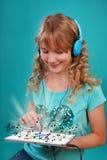 Muchacha que escucha la música en la tableta Fotografía de archivo