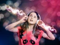 Muchacha que escucha la música en los auriculares Fotografía de archivo