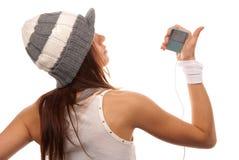 Muchacha que escucha la música en los auriculares blancos Imagen de archivo
