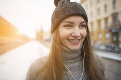 Muchacha que escucha la música en los auriculares blancos Imágenes de archivo libres de regalías