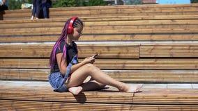 Muchacha que escucha la música en los auriculares usando el smartphone que se sienta en un banco con un buen humor en parque del  almacen de metraje de vídeo