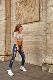 Muchacha que escucha la música en los auriculares y que baila en ciudad Imagen de archivo libre de regalías