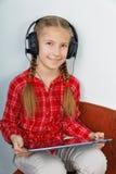 Muchacha que escucha la música en su Tablet PC Imagenes de archivo