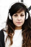 Muchacha que escucha la música mientras que se inclina en una pared Imagenes de archivo