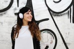 Muchacha que escucha la música mientras que se inclina en una pared Imagen de archivo