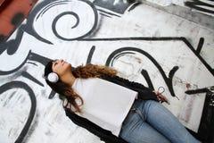Muchacha que escucha la música mientras que se inclina en una pared Fotos de archivo libres de regalías