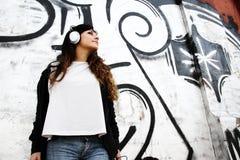 Muchacha que escucha la música mientras que se inclina en una pared Foto de archivo