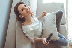 Muchacha que escucha la música mientras que se sienta en el sofá Imágenes de archivo libres de regalías