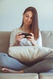 Muchacha que escucha la música mientras que se sienta en el sofá Imagen de archivo