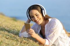 Muchacha que escucha la música que mira el contenido elegante del teléfono Imágenes de archivo libres de regalías