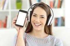 Muchacha que escucha la música que muestra la pantalla elegante en blanco del teléfono Imagenes de archivo