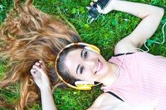 Muchacha que escucha la música que fluye con los auriculares Fotos de archivo libres de regalías
