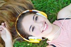 Muchacha que escucha la música que fluye con los auriculares en verano en a Imágenes de archivo libres de regalías