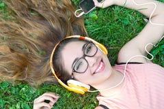 Muchacha que escucha la música que fluye con los auriculares en verano en a Imagenes de archivo
