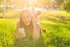 Muchacha que escucha la música que fluye con los auriculares en verano en un prado Fotos de archivo