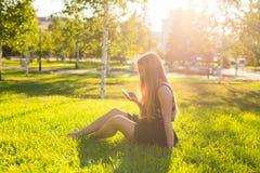 Muchacha que escucha la música que fluye con los auriculares en verano en un prado Imagenes de archivo