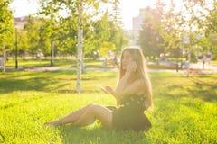 Muchacha que escucha la música que fluye con los auriculares en verano en un prado Foto de archivo