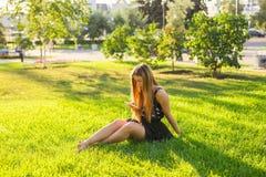 Muchacha que escucha la música que fluye con los auriculares en verano en un prado Foto de archivo libre de regalías
