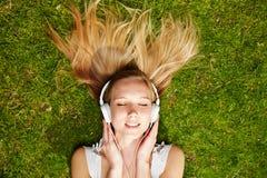 Muchacha que escucha la música que fluye en verano Foto de archivo