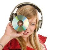 Muchacha que escucha la música que muestra el CD Foto de archivo libre de regalías