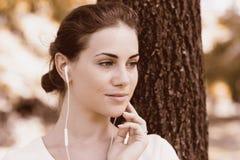 Muchacha que escucha la música que viene de los auriculares Imágenes de archivo libres de regalías