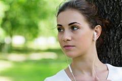 Muchacha que escucha la música que viene de los auriculares Foto de archivo