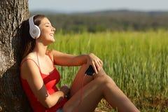 Muchacha que escucha la música relajada en un campo verde Imagenes de archivo