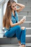 Muchacha que escucha la música, sentándose en los pasos Foto de archivo libre de regalías