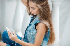 Muchacha que escucha la música, sentándose en los pasos Fotografía de archivo libre de regalías
