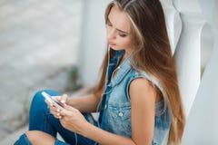 Muchacha que escucha la música, sentándose en los pasos Imagenes de archivo