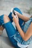 Muchacha que escucha la música, sentándose en los pasos Imagen de archivo libre de regalías