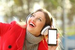 Muchacha que escucha la música y que muestra la pantalla del smartphone Fotos de archivo libres de regalías