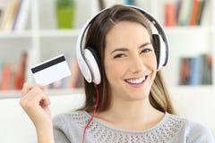 Muchacha que escucha la música y que muestra la tarjeta del crédito en blanco Foto de archivo