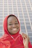Muchacha que escucha la música y que sonríe en la calle, trece años Foto de archivo libre de regalías