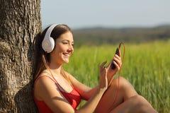 Muchacha que escucha la música y que transfiere canciones en un campo Imagen de archivo libre de regalías