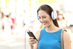 Muchacha que escucha los auriculares que llevan de la música en la calle Fotos de archivo