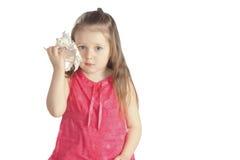 Muchacha que escucha un seashell Imagen de archivo