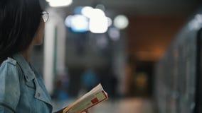 Muchacha que espera su tren y que lee un libro, cámara lenta almacen de video