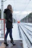 Muchacha que espera un tren en el ferrocarril Foto de archivo libre de regalías