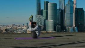 Muchacha que estira en el tejado contra el contexto de la ciudad metrajes