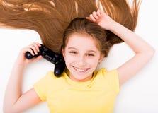 Muchacha que estira en piso con la palanca de mando a disposición Imagen de archivo