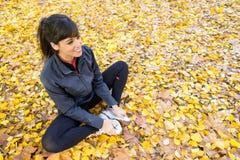 Muchacha que estira las piernas en otoño Imágenes de archivo libres de regalías