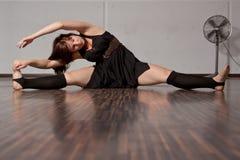 Muchacha que estira sus piernas Imagen de archivo libre de regalías