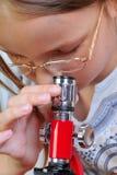 Muchacha que estudia algo con el microscopio foto de archivo