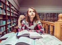 Muchacha que estudia difícilmente en biblioteca Fotografía de archivo