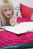 Muchacha que estudia en cama Imagenes de archivo