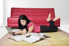 Muchacha que estudia en la alfombra con el ordenador portátil y los libros Imagenes de archivo