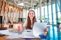 Muchacha que estudia en la cantina de universidad fotos de archivo libres de regalías