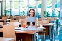 Muchacha que estudia en la cantina de universidad Fotografía de archivo libre de regalías